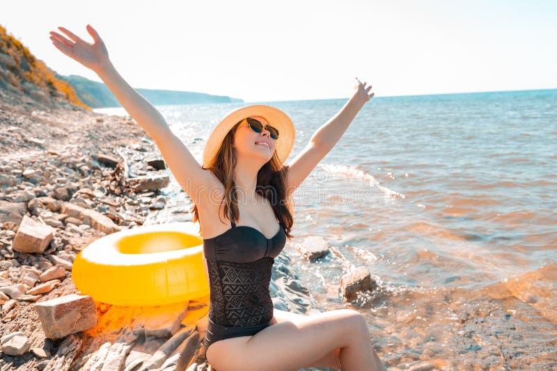 Une jeune jolie femme profite du reste, assise sur le rivage rocheux de la mer à côté du cercle de natation Le concept de vacance images libres de droits