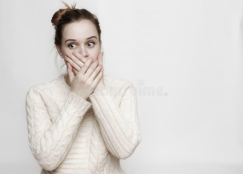 Une jeune jolie fille avec de grands yeux a couvert sa bouche de son Han image libre de droits