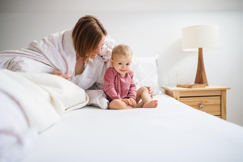 Une jeune mère avec peu de fille s'asseyant à l'intérieur sur le lit le matin, jouant photos stock