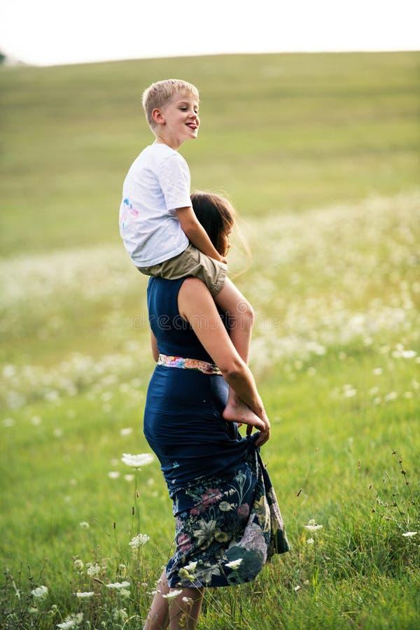 Une jeune mère donnant le tour de ferroutage au petit fils en nature un jour d'été image stock