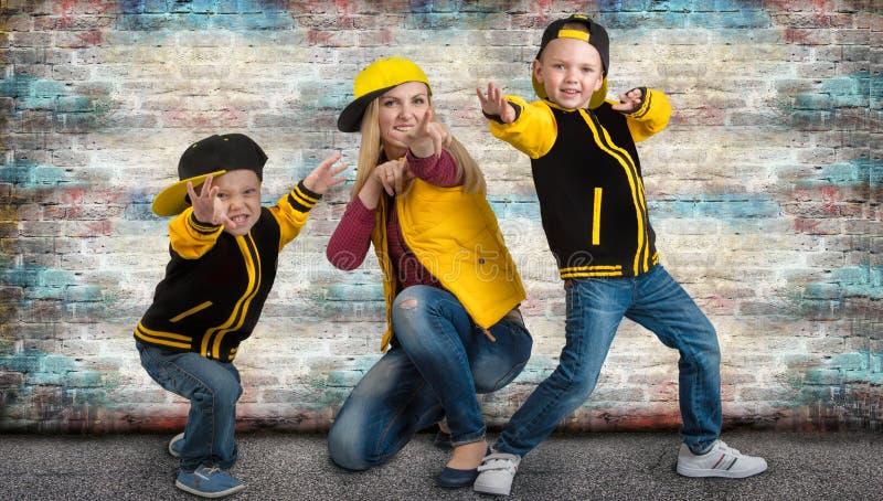 Une jeune mère et deux jeunes fils dans le style de hanche sautent à cloche-pied Famille à la mode Graffiti sur les murs image stock