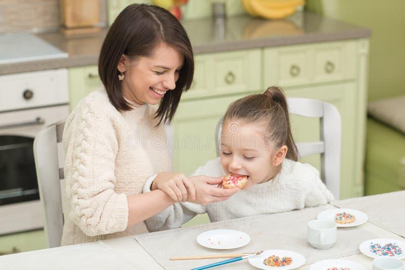 Une jeune mère et ses biscuits de essai de fille photo stock