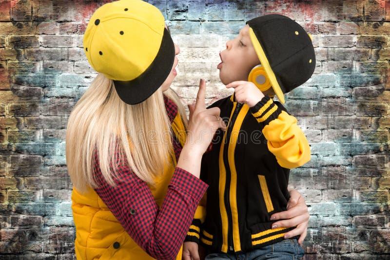 Une jeune mère et un petit fils dans le style de l'houblon de hanche Famille à la mode Le jeune frappeur Le DJ frais photo libre de droits