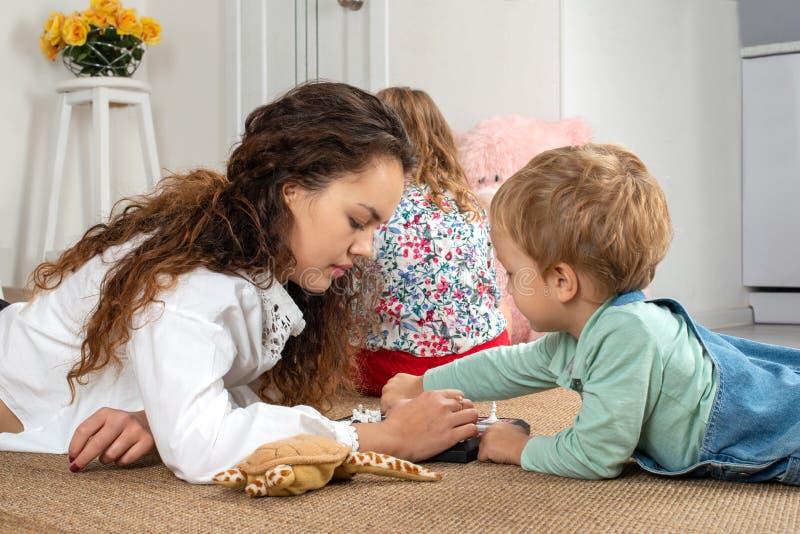 Une jeune mère ou bonne d'enfants ou une soeur plus âgée se trouve sur le plancher sur photos stock