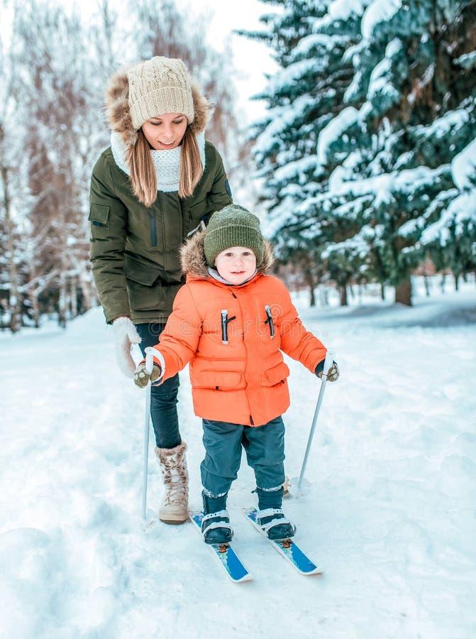 Une jeune mère s'assure qu'un enfant de dos sur des enfants skie jeune fils de 3-5 années, en hiver dans la ville contre le conte images libres de droits