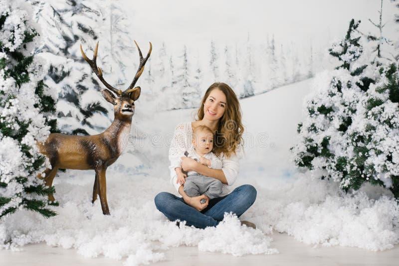 Une jeune mère tient son jeune fils dans les bras, ils s'assoient dans la neige artificielle dans la zone de photos d'hiver images stock