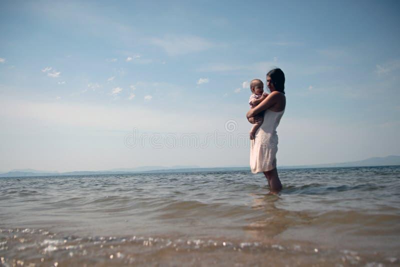 Une jeune mère tient un enfant dans des ses bras se tenant en mer image libre de droits