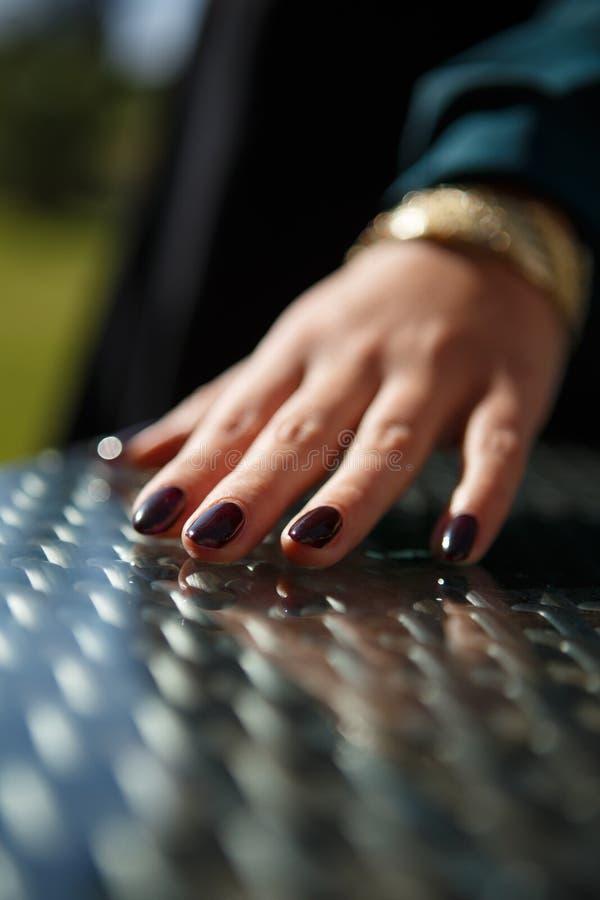 Une jeune main femelle avec le vernis à ongles scintillant foncé image stock