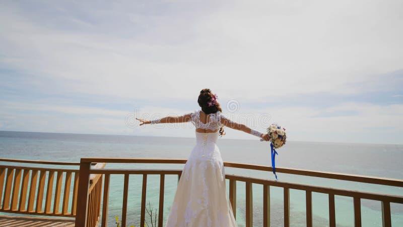 Une jeune mariée éblouissante apprécie le bonheur de la taille du balcon donnant sur l'océan et les récifs Vol de l'amour exotiqu image stock
