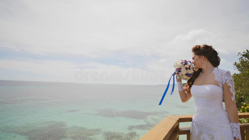 Une jeune mariée éblouissante apprécie le bonheur de la taille du balcon donnant sur l'océan et les récifs Vol de l'amour exotiqu photo stock