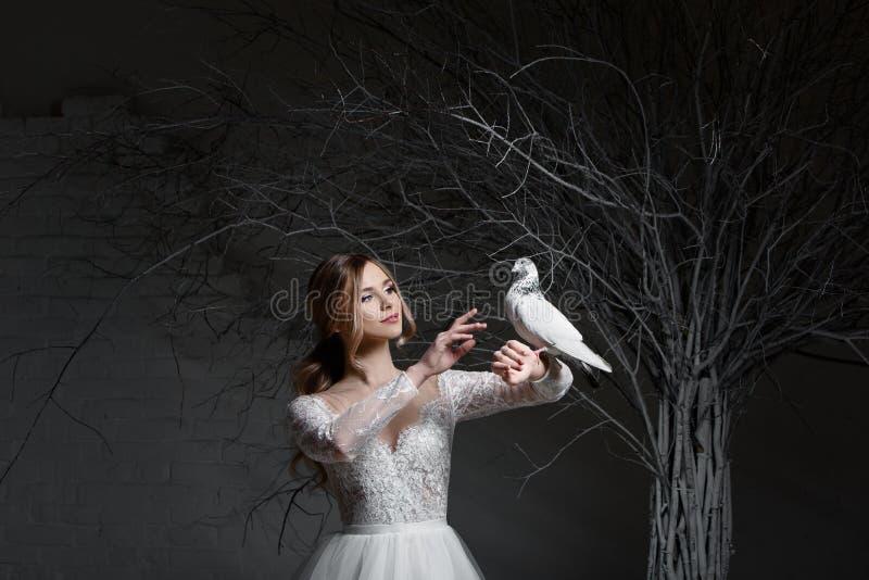 Une jeune jeune mariée blonde dans la robe de mariage blanche sur un fond des murs blancs et l'arbre blanc à l'arrière-plan tient photographie stock