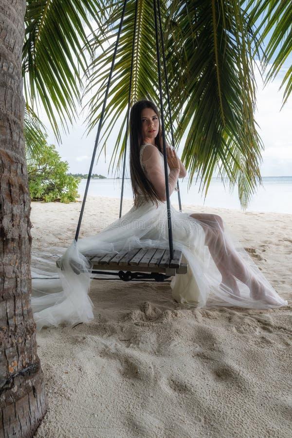 Une jeune mariée dans une robe blanche monte sur une oscillation sous un grand palmier image stock