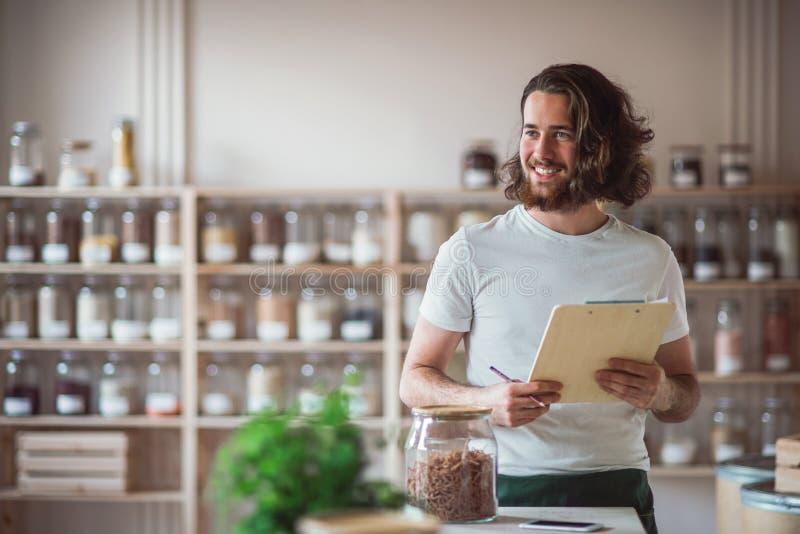 Une jeune position masculine d'employé de magasin dans le magasin de rebut zéro, vérifiant des actions images libres de droits