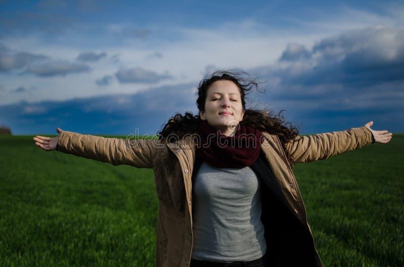 Une joie de sentiment de fille et heureux dans le domaine vert avec des nuages photo stock