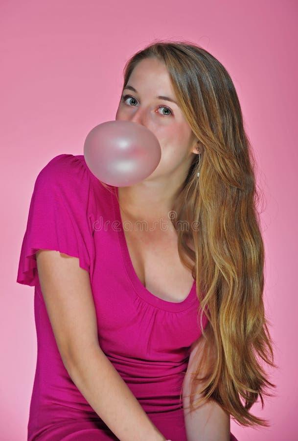 Une jolie adolescente soufflant une bulle image stock