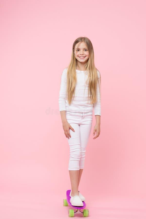 Une jolie bonne fille de patineur Petite position mignonne de fille sur la planche à roulettes sur le fond rose Peu enfant de fil photo libre de droits