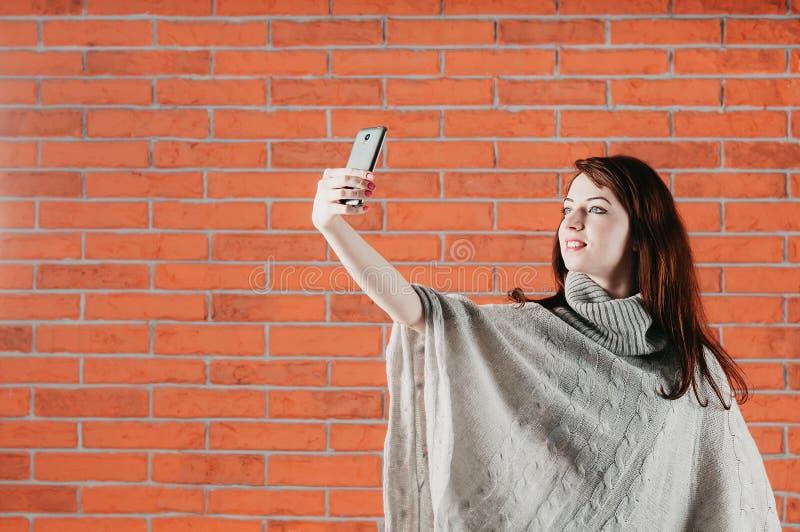 Une jolie fille dans le pull gris fait le selfie avec le smartphone, photo libre de droits