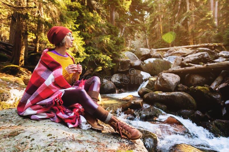 Une jolie fille de hippie avec un plaid de plaid sur ses épaules dans un chapeau et un chandail jaune et verres avec une tasse de image libre de droits