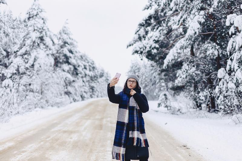 Une jolie fille fait un selfie au milieu d'une forêt neigeuse roa image libre de droits