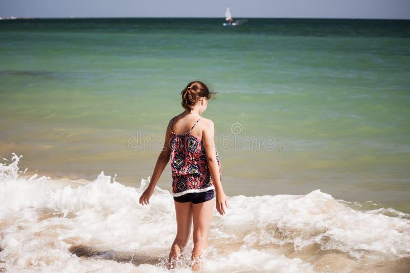 Une jolie fille jouant dans les vagues sur la plage, foyer mou, concept de plage photographie stock libre de droits