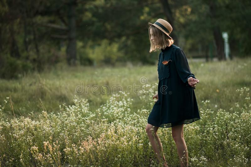 Une jolie fille marche le long du gisement de fleur images stock