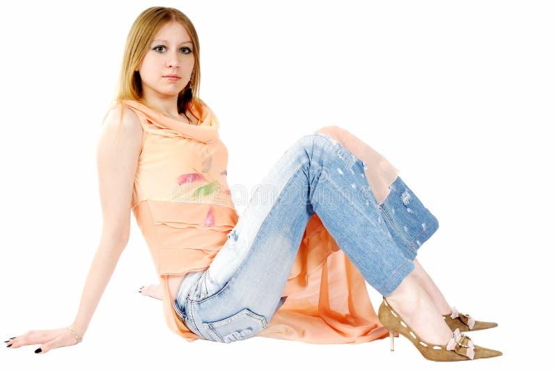 Une jolie fille s'asseyant sur l'étage image libre de droits