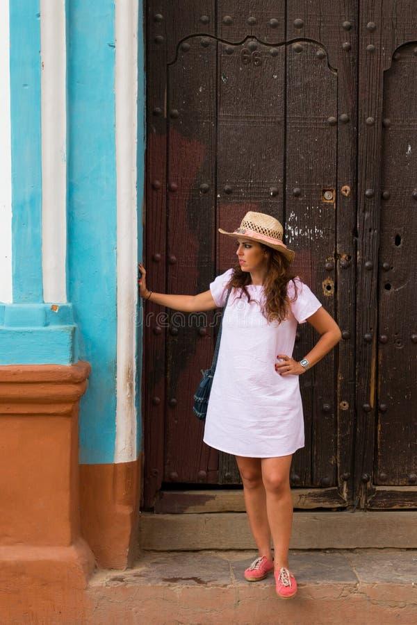 Une jolie jeune femme avec le chapeau situé à la porte d'une vieille maison coloniale dans la ville coloniale de Trinidad Cuba images stock