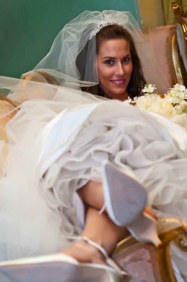 Une jolie mariée Lauing vers l'arrière dans un canapé images libres de droits