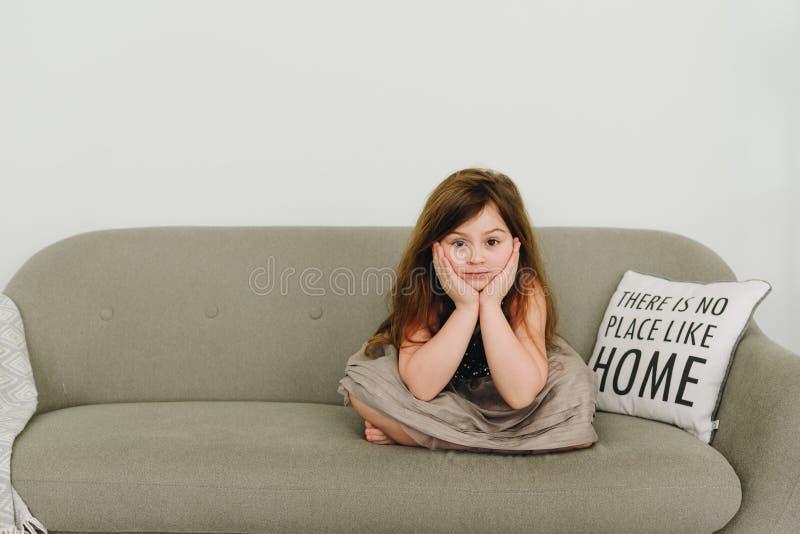 Une jolie petite fille s'asseyant sur le sofa dans la pose de lotus photo libre de droits