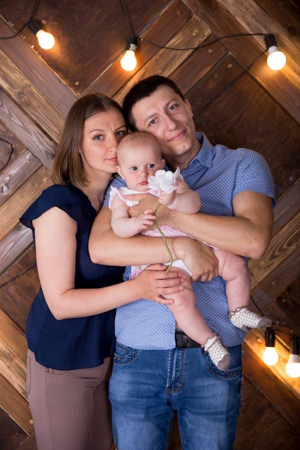 Une joyeuse jeune famille caucasienne publie en studio image stock