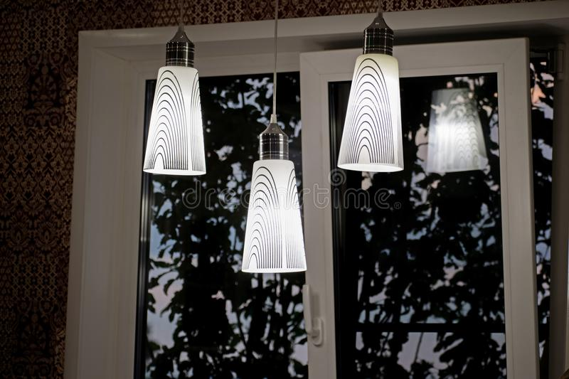 Une lampe décorative blanche pend du plafond Un lustre moderne dans la cuisine photographie stock libre de droits