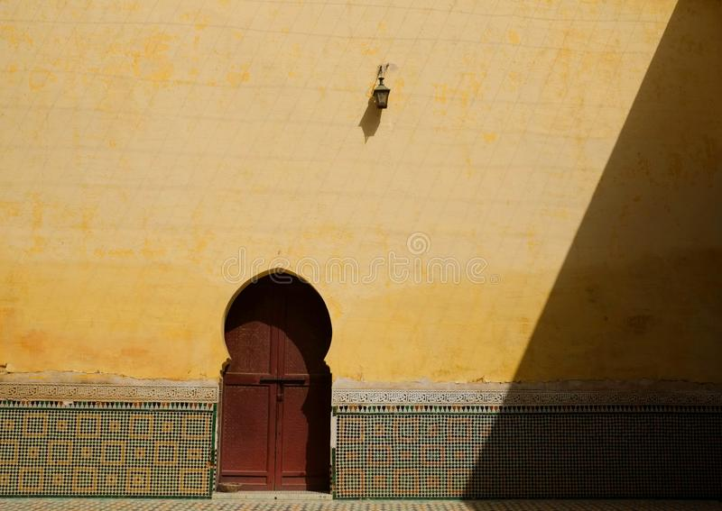 Une lampe de vintage sur le mur jaune au-dessus des tuiles rouges marocaines de porte et de zellige fonctionnent image stock