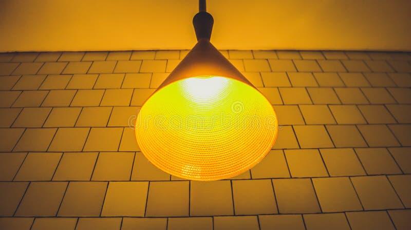 Une lampe jaune de salle de bains avec la ligne mur de modèle comme fond photographie stock
