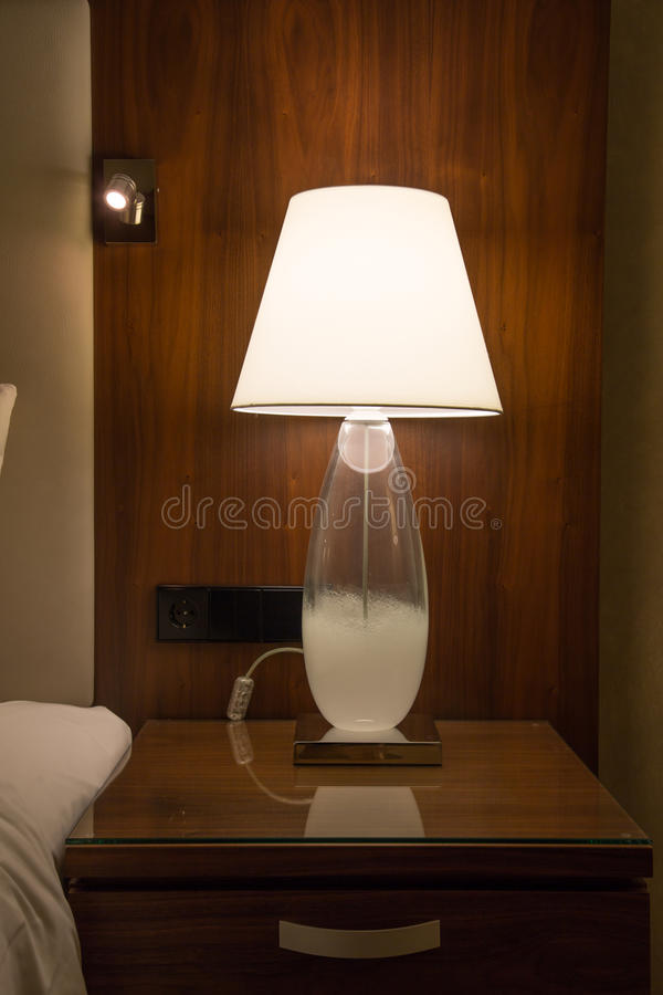 Une lampe sur un coffret de chevet images libres de droits