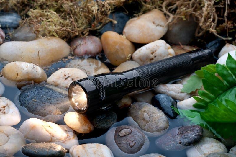 Une lampe-torche noire dans un petit flot photographie stock libre de droits