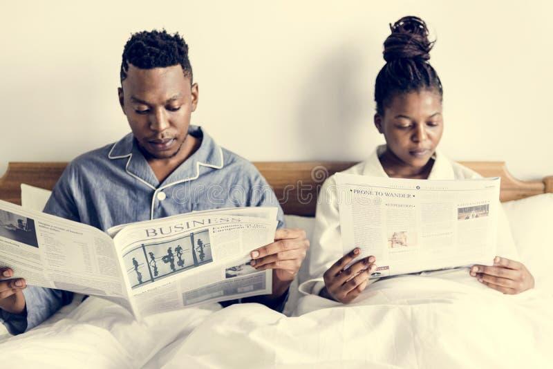 Une lecture heureuse de couples dans le lit images stock