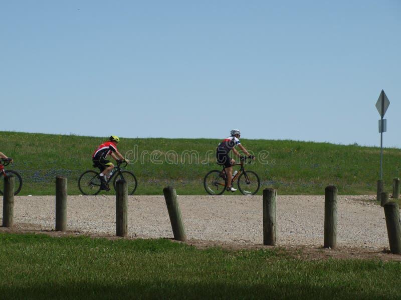 Une ligne des cyclistes montent la traînée blanche de roche images stock