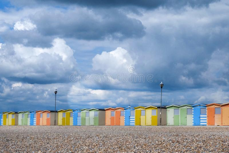 Une ligne des huttes de plage sur un Pebble Beach images stock