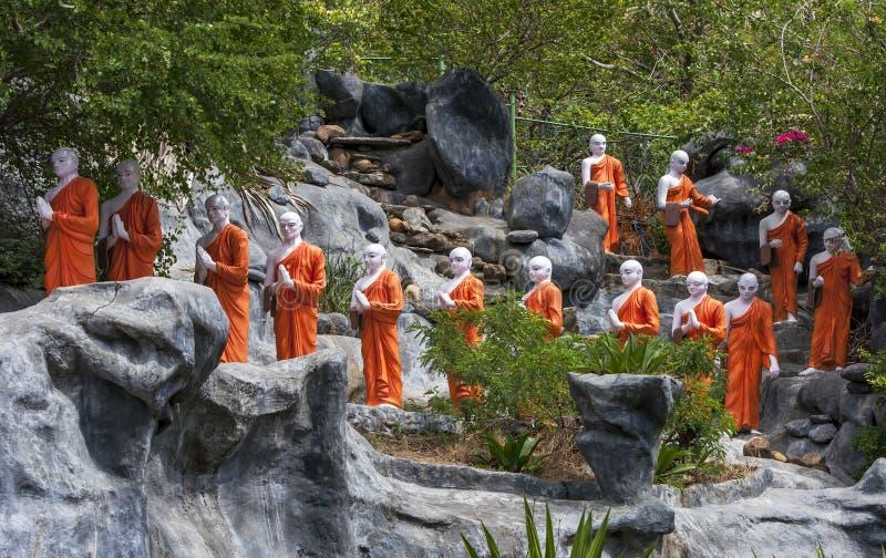 Une ligne des statues de moine bouddhiste approchant le le temple d'or chez Dambulla, Sri Lanka image libre de droits