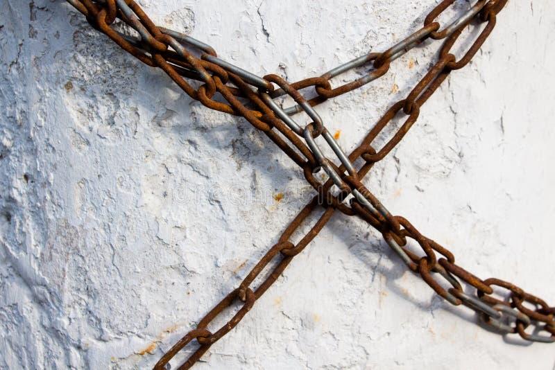 Une longue chaîne faite de métal est couverte de peu de rouille enroulée autour du mur en béton et interdit n'importe quel mouvem images stock