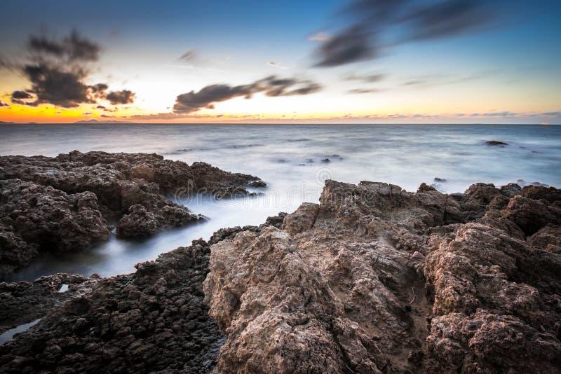 Une longue exposition a tiré d'une mer au crépuscule avec des rochers comme premier plan et à une combinaison de couleurs chaudes photo libre de droits