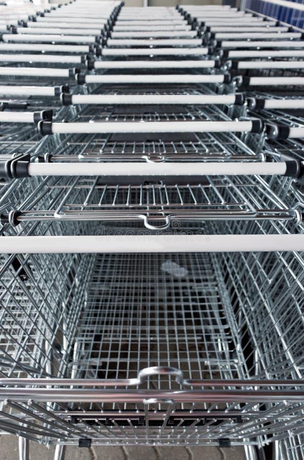 Une longue rangée de trolleys près du supermarché photos stock