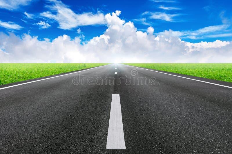 Une longue route droite et un ciel bleu images libres de droits