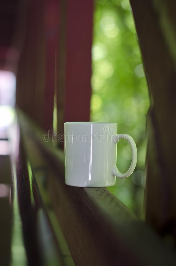 Une longue tasse de café blanc vide soloe le long d'un pont photo stock
