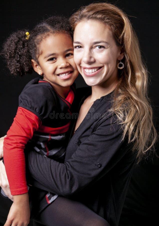 Une mère de famille avec l'enfant de fille posant sur un studio noir de fond images stock