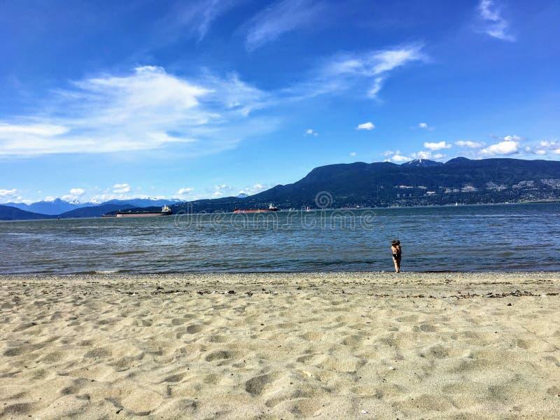 Une mère et une fille marchant le long de la plage sablonneuse des banques espagnoles, avec l'océan et les montagnes à l'arrière- images stock
