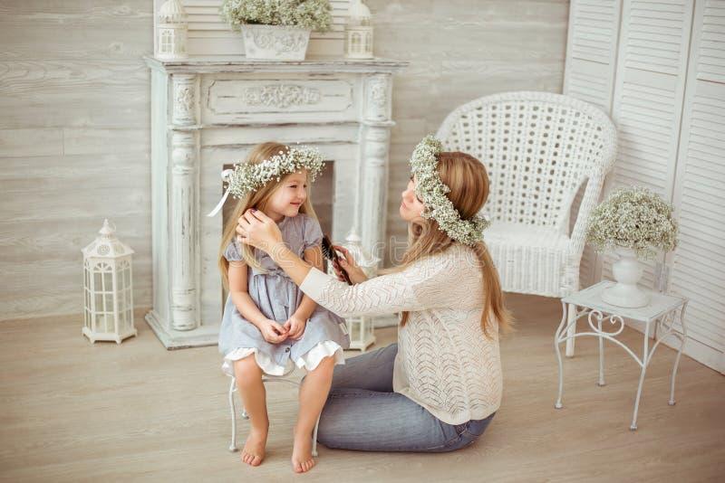 Une mère heureuse peigne les cheveux de sa fille photos libres de droits