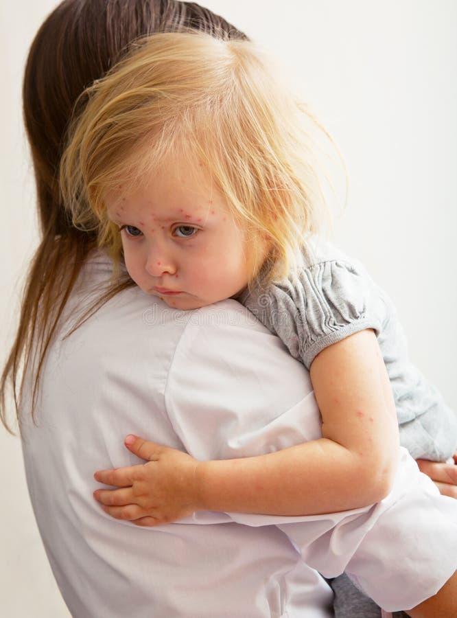 Une mère retient une fille malade. images libres de droits