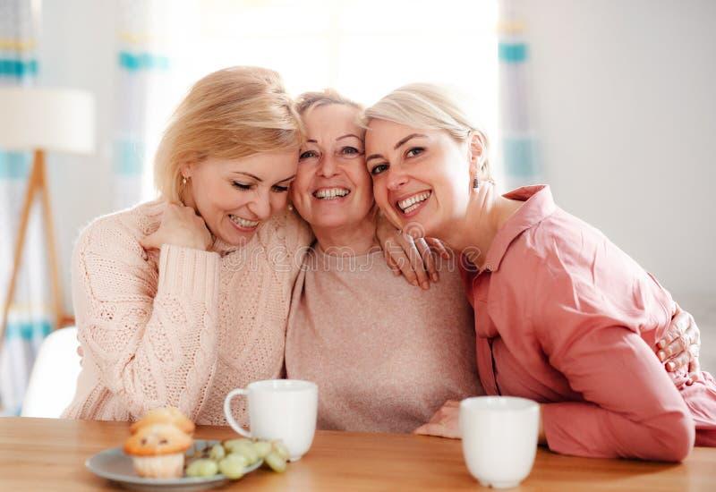 Une mère supérieure avec deux filles adultes s'asseyant à la table à la maison photographie stock libre de droits