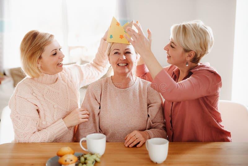 Une m?re sup?rieure avec deux filles adultes s'asseyant ? la table ? la maison, ayant l'amusement image stock
